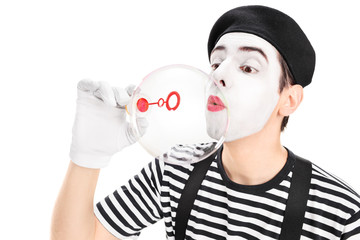 Mime artist blowing a bubble through wand