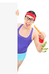 Nerdy man in sportswear eating carrot behind panel