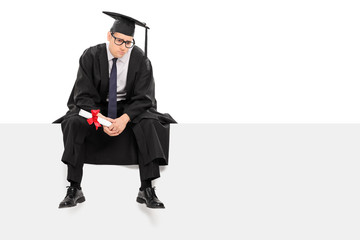 Worried graduate student sitting on a signboard