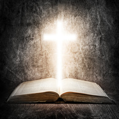 Old Bible and illuminated cross