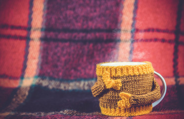 Knitted  yellow cup  at red rug background
