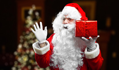 Happy Santa Claus holding a gift