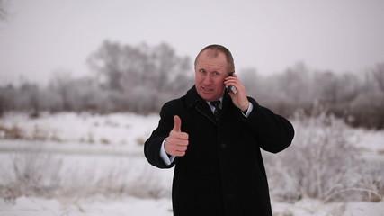 businessman  take good news on  mobile. Winter portrait
