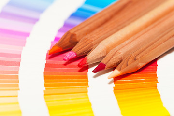 crayons de couleur orange sur un nuancier de teintes rose violet