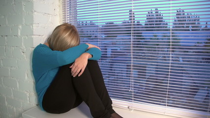 sad beautiful woman sitting near the window, dolly, slow motion