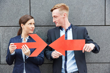 Business man and woman holding arrows against each other