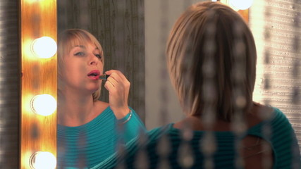 beautiful woman paints her lips, slow motion, dolly 2