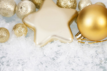 Golden Christmas balls and star on icy background