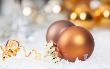 Golden Christmas balls on icy background