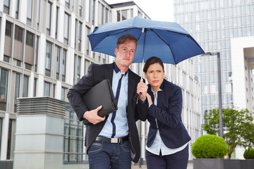 Business people in the rain under umbrella in the city