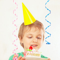 Young boy in festive hat tasting a piece of birthday cake
