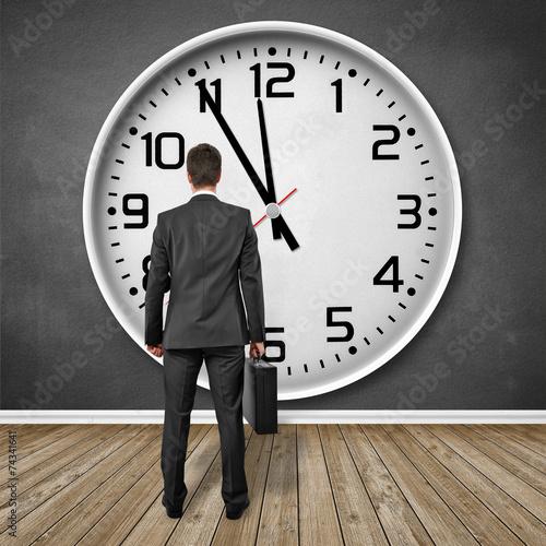 Mann steht vor einer Uhr!