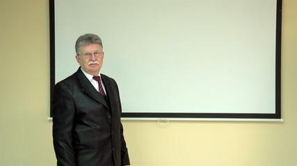 elderly businessman organizes a presentation in the office