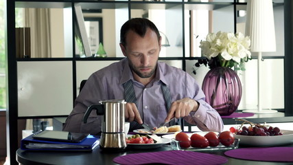 Handsome businessman eating breakfast by table at home