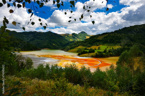 Leinwanddruck Bild flooded church in toxic red polluted  lake due to copper mining,