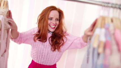 Young redhead woman looking through clothing, slow motion