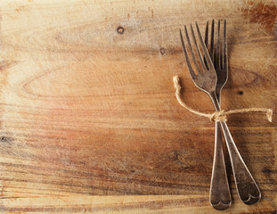 two fork tied by string on old wood, background