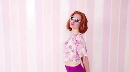 Young woman wearing sunglasses playfully dances to the camera