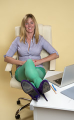 Secretary sitting on office chair relaxing with legs on desk