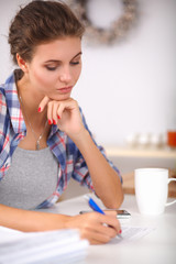 Beautiful young woman writing something in her note pad