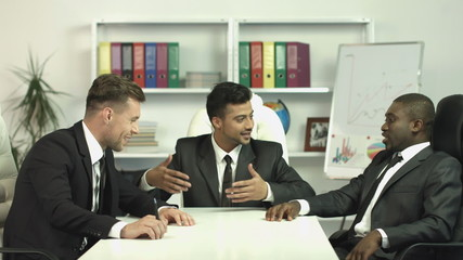 The businessmen have a rest in the office talk, laugh and smile