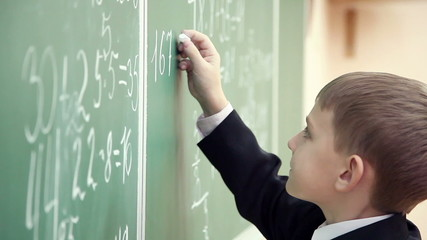 little boy solves math on the blackboard at school 2