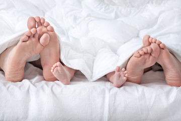 Funny family feet under the white blanket