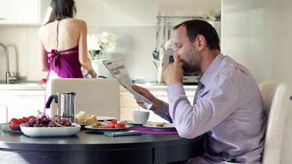 Businessman reading newspaper while his wife cooking in the kitc