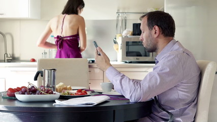 Businessman sitting with smartphone by the table and talking wit
