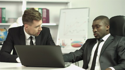 The businessmen discuss the project drawing on the laptop screen