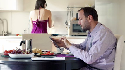 Businessman working with tablet while his wife cooking in the ki