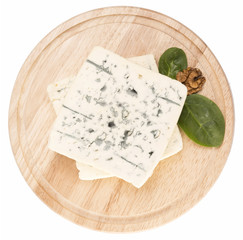 blue cheese decorated with arugula and walnut on wooden board is