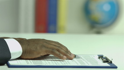 The businessman read and sign the contract papers