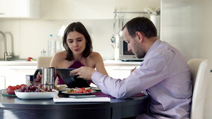 Couple by the table, man showing something to his wife on tablet