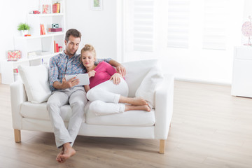 couple relaxing on a couch and using a digital tablet