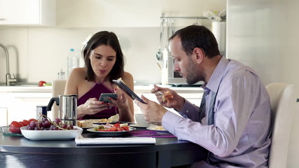 Young couple sitting with tablet and smartphone by the table