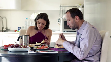 Young couple talking during breakfast in the kitchen
