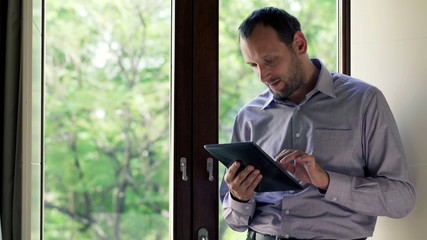 Handsome man standing with tablet by the window at home