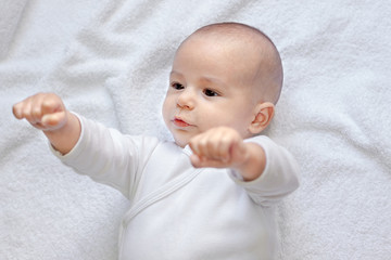 Strong healthy baby looking at fists