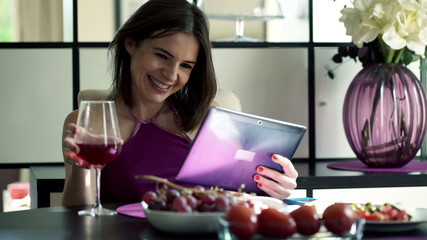 Happy  woman watching movie on tablet  by the table at home