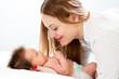 Happy mother cuddling her newborn baby