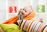 Fototapety kid boy playing on pillows in bedroom