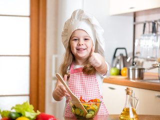 kid girl preparing food and showing thumb up