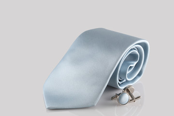 blue tie with cuff links on white background