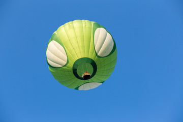 Green hot air balloon on blue sky background