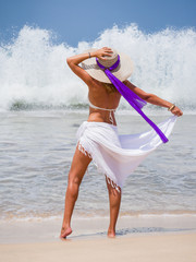 woman on beach with tropical sarong and hat