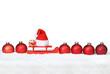 Weihnachtshintergrund mit Kugeln / Mütze und Schnee