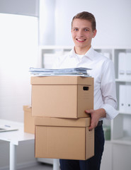 Young Man holding a stack of cardboard boxes standing in office