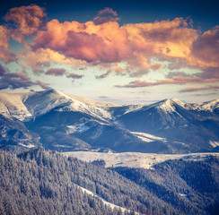 Winter alpine sunset in the mountains with dramatic sky
