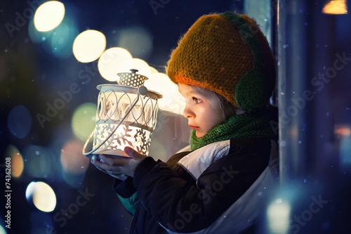 Leinwanddruck Bild Cute boy, holding lantern outdoor